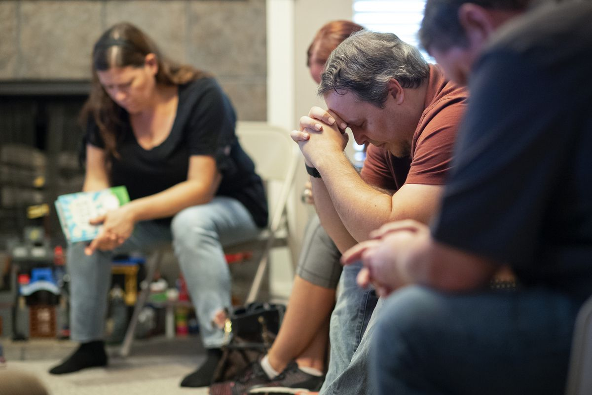 Andy Hogue bows his head in prayer during a church service in his home in Leander, Texas, on Sept. 6, 2020.