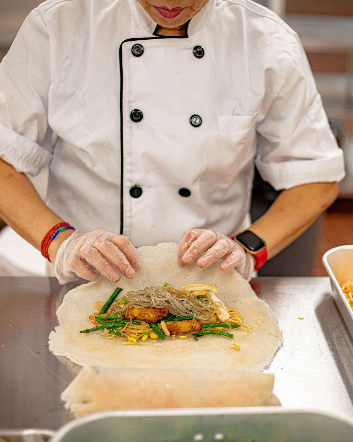 A woman in a chef's coat rolling meat and vegetables into a wrap