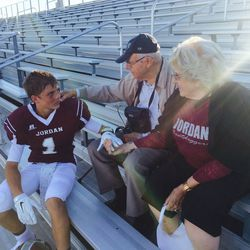 Zach Wilson, left, sits in the stands with his grandparents, Gary and Rose Neeleman, during his freshman season at Jordan High. Wilson later transferred to Corner Canyon.