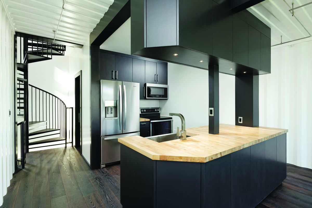 Kitchen with black cabinets, stainless steel appliances, and wooden counter.