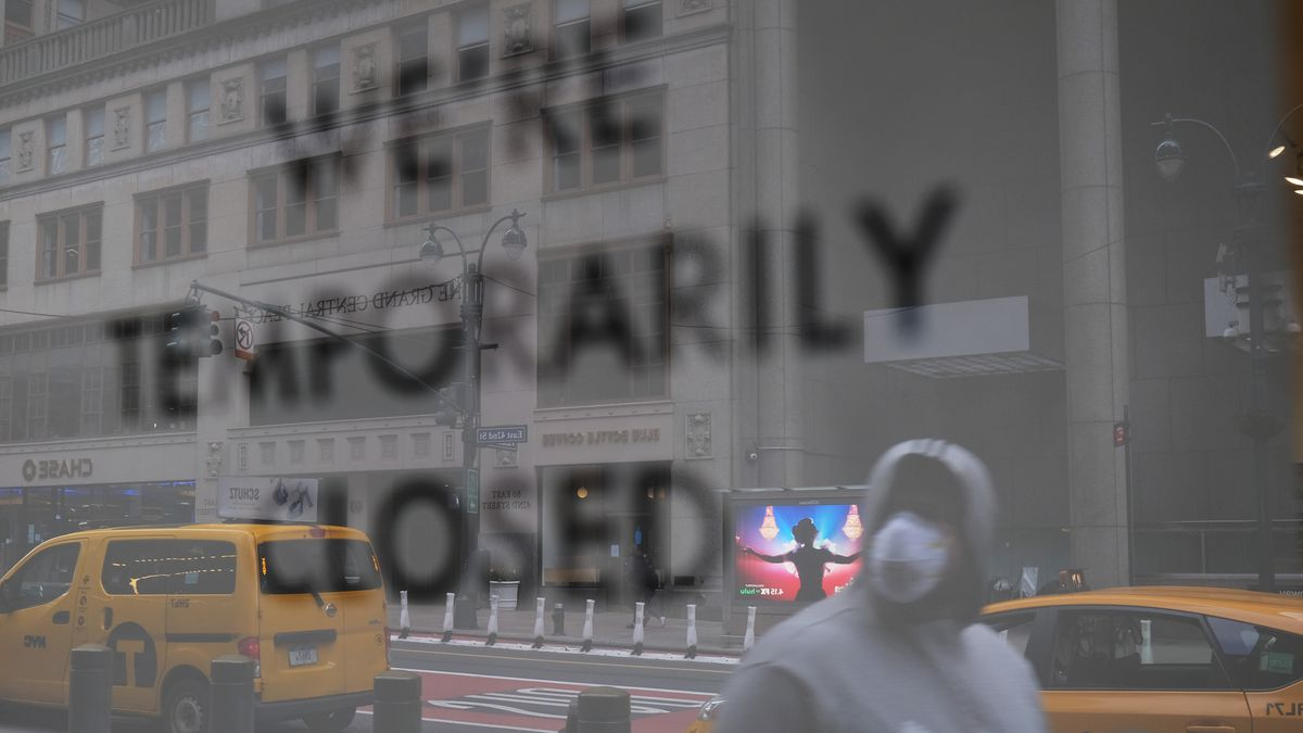 """A man in a mask walking by a storefront that reads """"We're temporarily closed."""""""