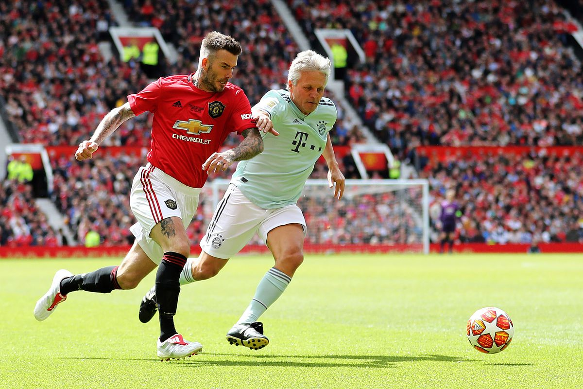 MANCHESTER, ENGLAND - MAY 26: David Beckham of Manchester United '99 Legends beats Andreas Ottl of FC Bayern Legends during the Manchester United '99 Legends and FC Bayern Legends match at Old Trafford on May 26, 2019 in Manchester, England.