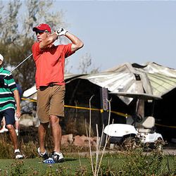 Brian Wangsgard, left, and Jim Riddle play golf at Wingpointe Golf Course in Salt Lake City Friday. The restroom at Hole 13, background, was destroyed Thursday in a wildfire.