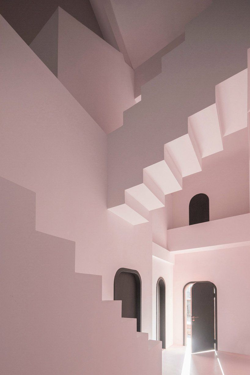 Room with pink stairs and black doors