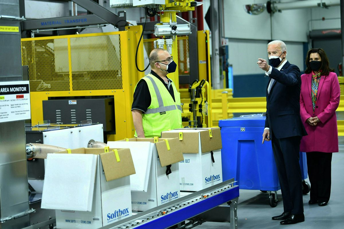 US President Joe Biden (C), with Michigan Governor Gretchen Whitmer (R) tours Covid-19 vaccine freezers at a Pfizer manufacturing site on February 19, 2021, in Portage, Michigan.
