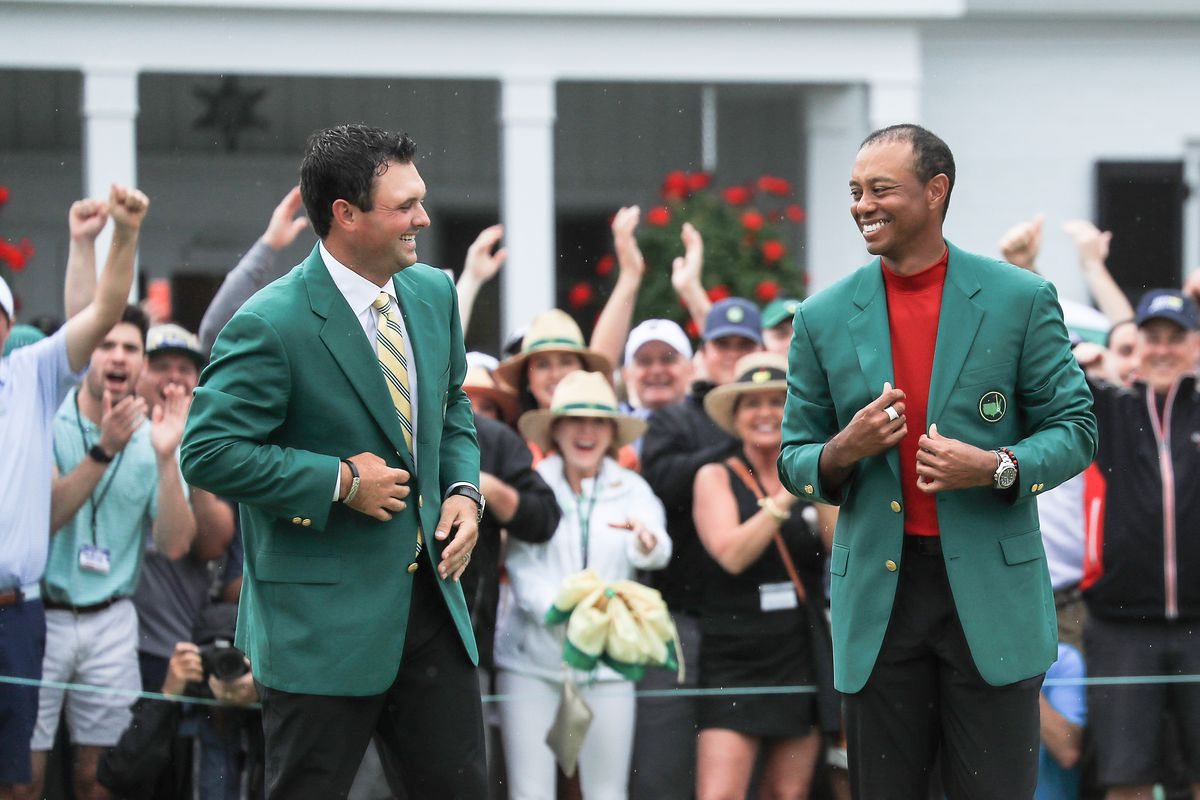 Tiger Woods of the United States is presented with his Green Jacket by 2018 Champion Patrick Reed during the Green Jacket presentation after his historic one shot win during the final round of the 2019 Masters Tournament at Augusta National Golf Club on April 14, 2019 in Augusta, Georgia.