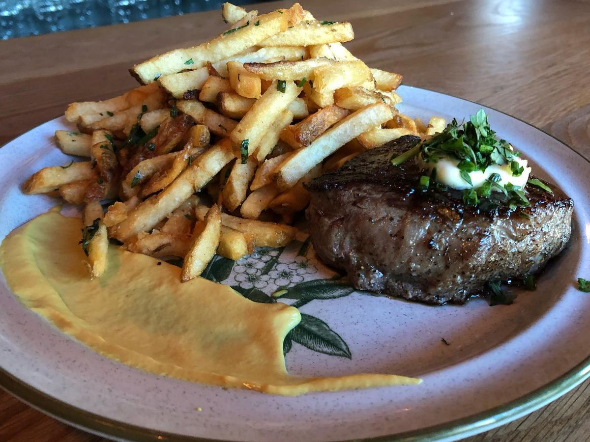 A plate of fries with a smear of mustard and a steak cut topped with butter and greens
