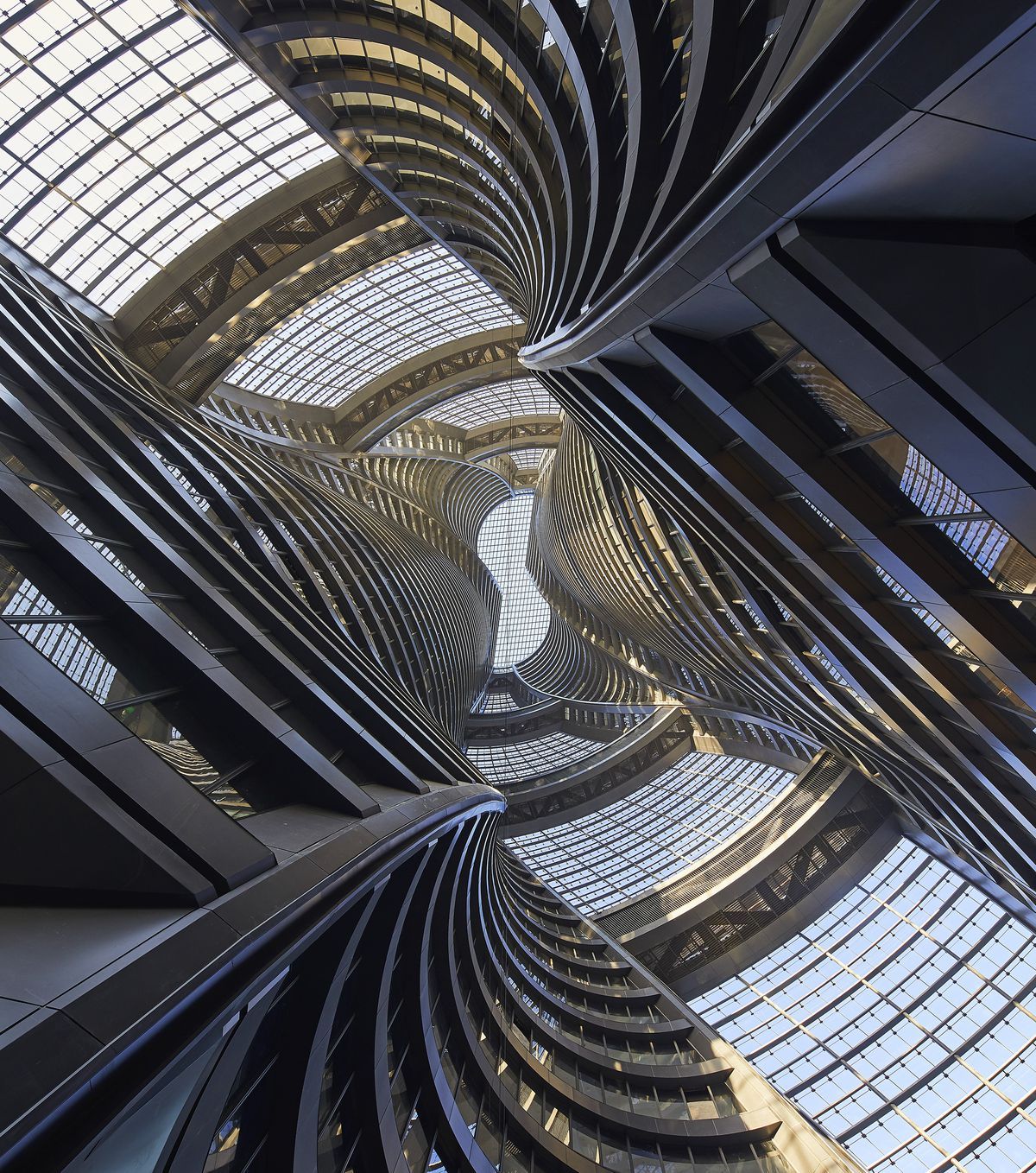 Photo looking up at an atrium in a glass tower.