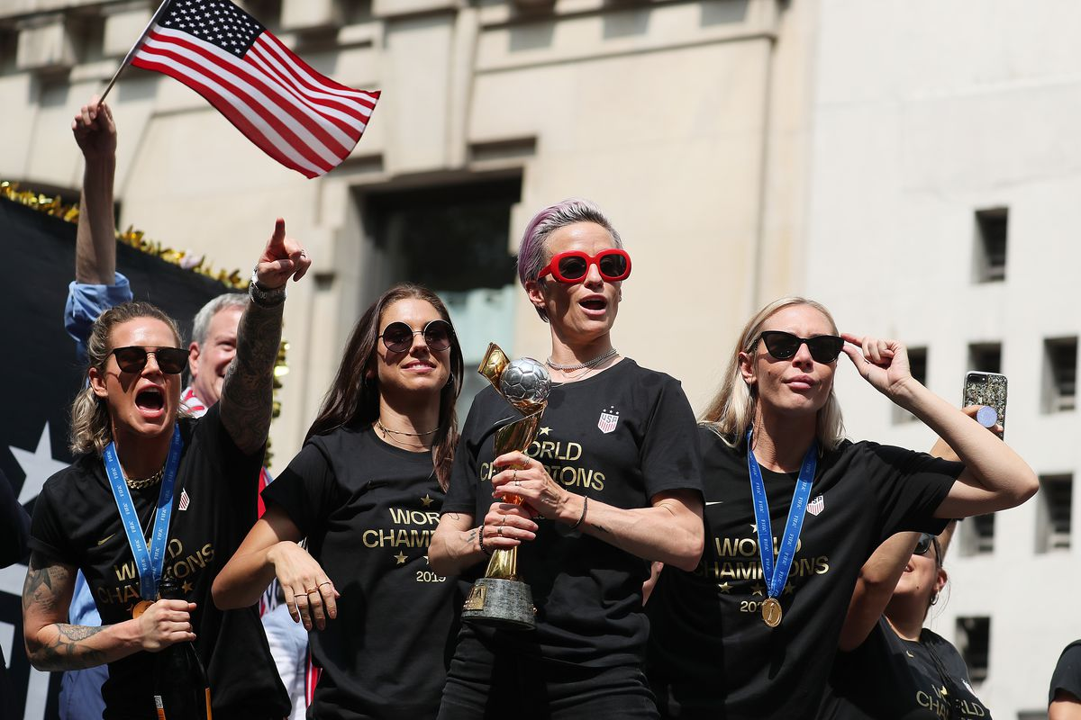 Megan Rapinoe (holding trophy) celebrates with teammates Ashlyn Harris, Alex Morgan, and Allie Long during the U.S. women's national soccer team Victory Parade and City Hall Ceremony on July 10, 2019 in New York City