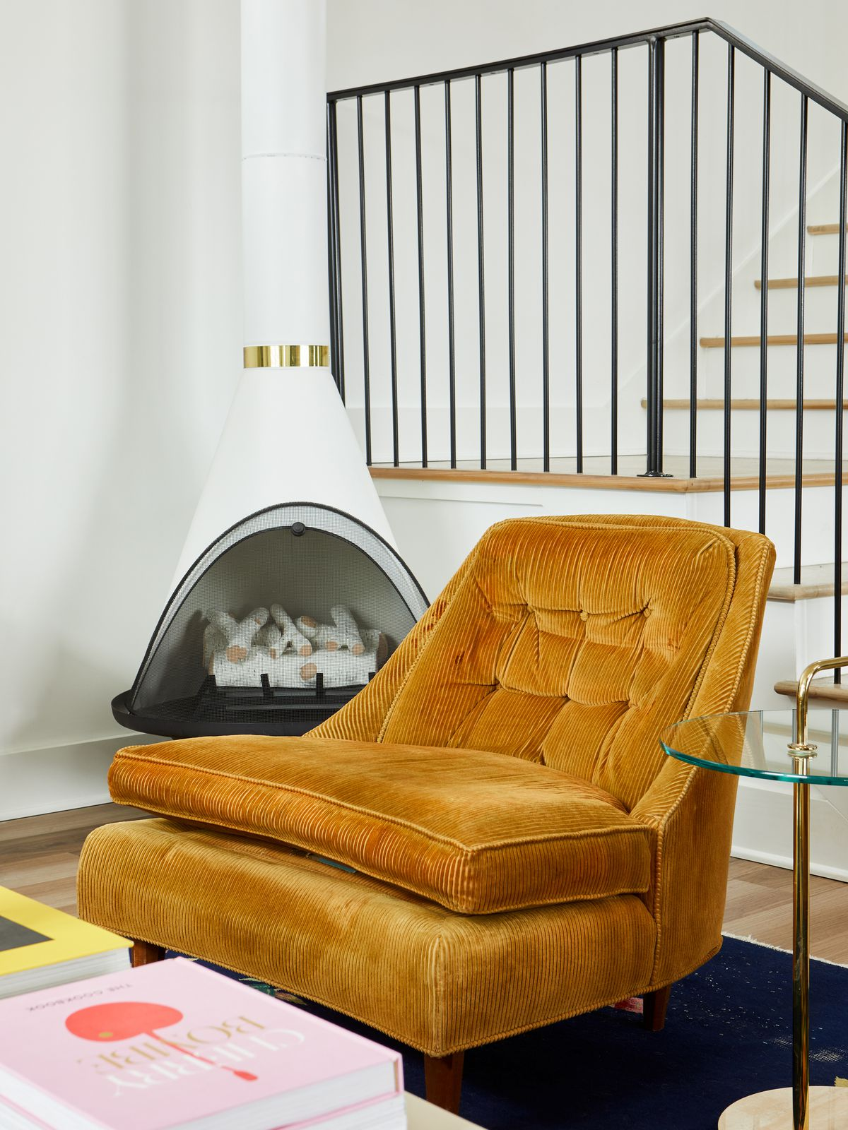 A large orange armchair is next to a white fireplace and in front of a staircase. There is a dark blue rug on the floor.