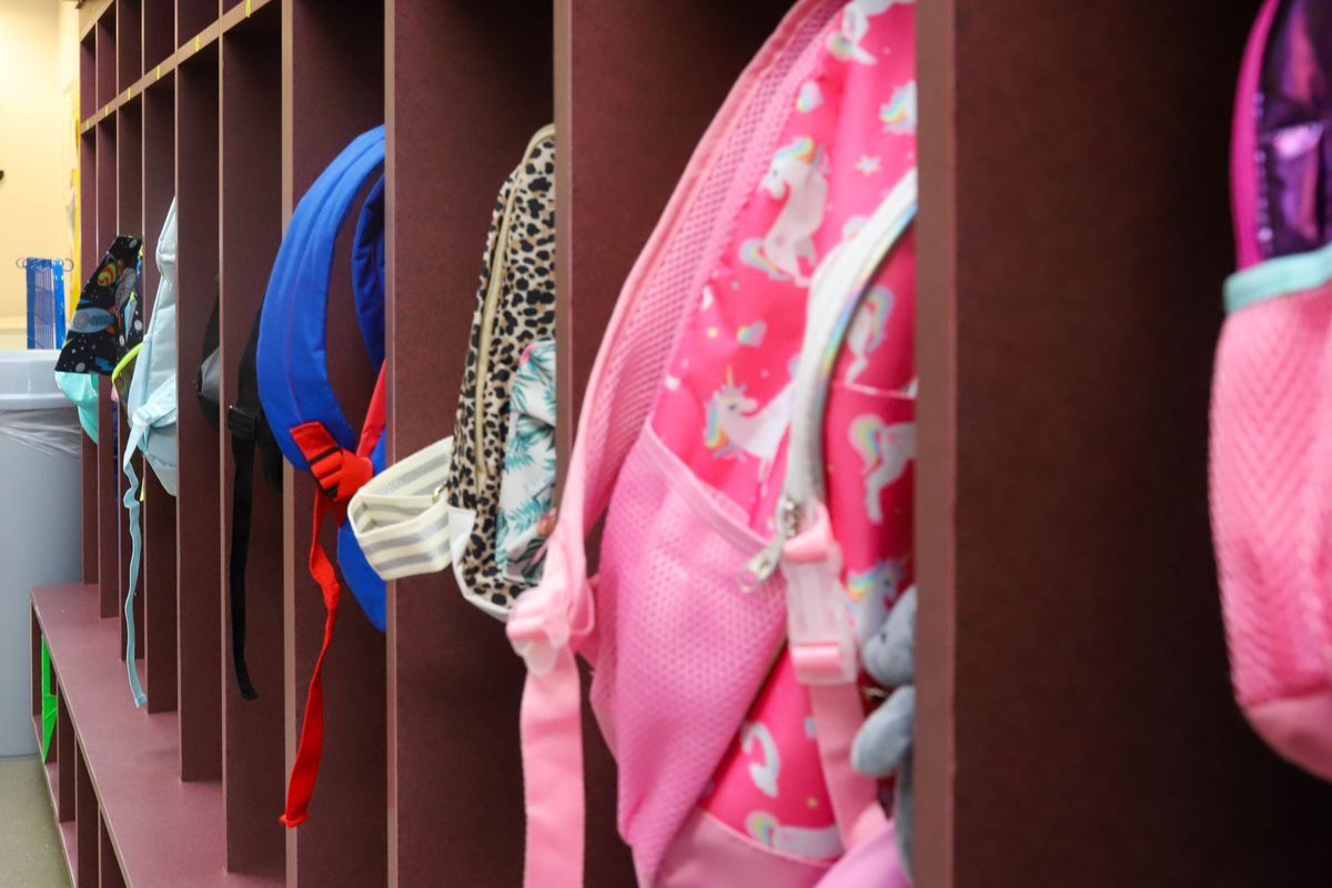 A child's pink backpack hangs off a coat rack.