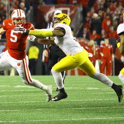Tanner McEvoy stiff arms a defender