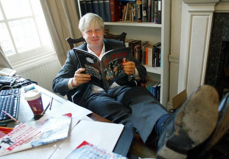 Boris Johnson, editor of the Spectator magazine at the time, sits in his London office reading the anniversary issue of the magazine to mark 175 years of publication, on September 25, 2003.
