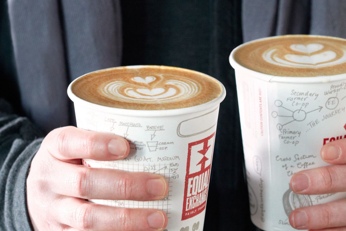 Two hands hold paper cups of coffee with Equal Exchange branding