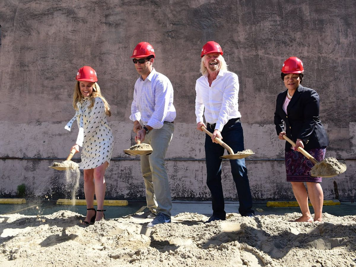 Four people wearing red hard hats plunge shovels into a dirt mound to mark a groundbreaking.