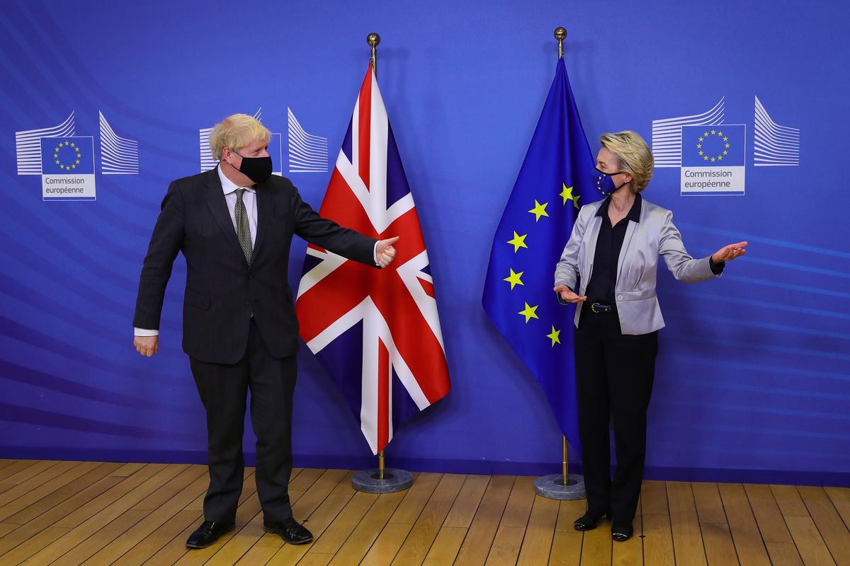 UK Prime Minister Boris Johnson and European Commission President Ursula von der Leyen standing in front of a UK flag and an EU flag.