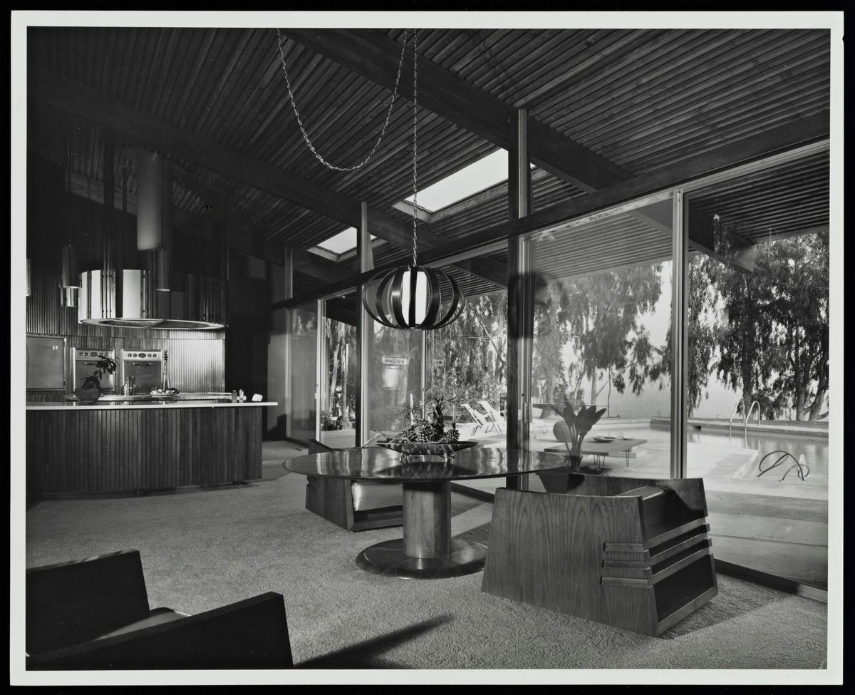 Black and white photo showing interior of the house with block armchairs and a glass table.