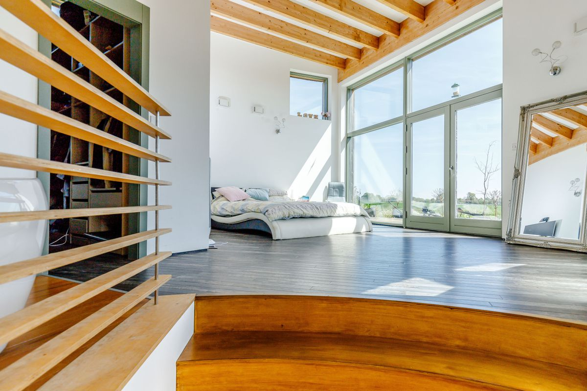 Master suite with wood floors and high ceiling.