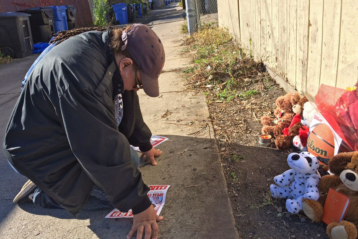 A woman stops to pray at a memorial to Tyshawn Lee the day after the fourth-grader was gunned down.