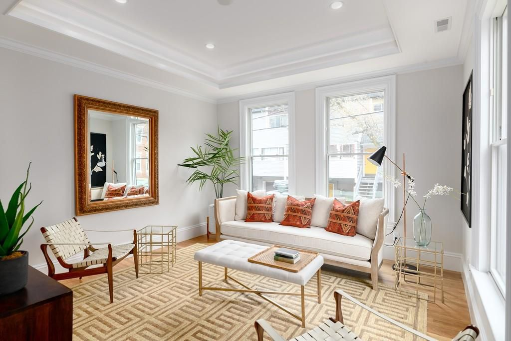 An airy, bright living room with furniture and two windows.