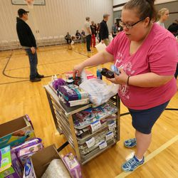 Amanda Bailey picks up hygiene items at an LDS stake center, where she is being temporarily housed during Tropical Storm Harvey in Houston on Tuesday, Aug. 29, 2017.