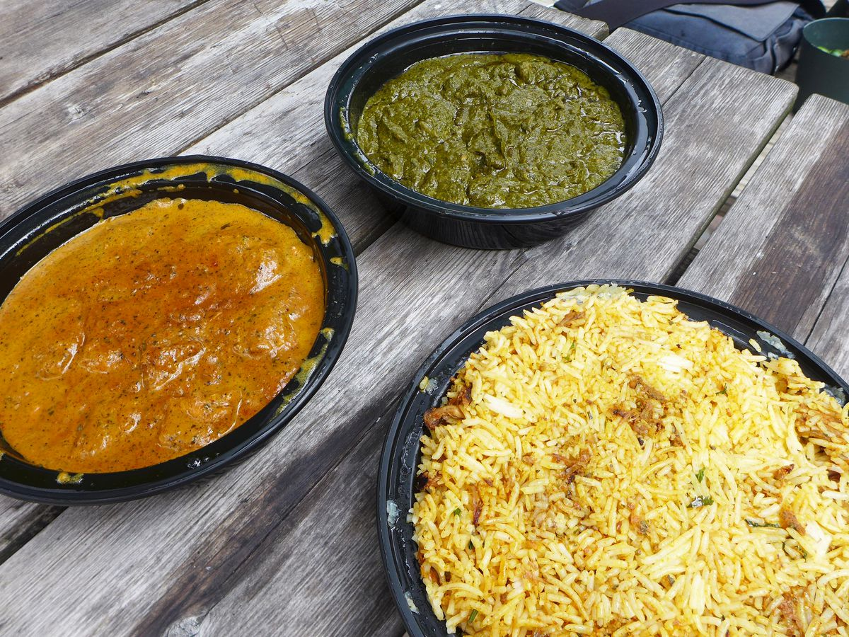 Three Indian dishes in plastic containers on a worn picnic table top, one green, one brown, and one rice based.