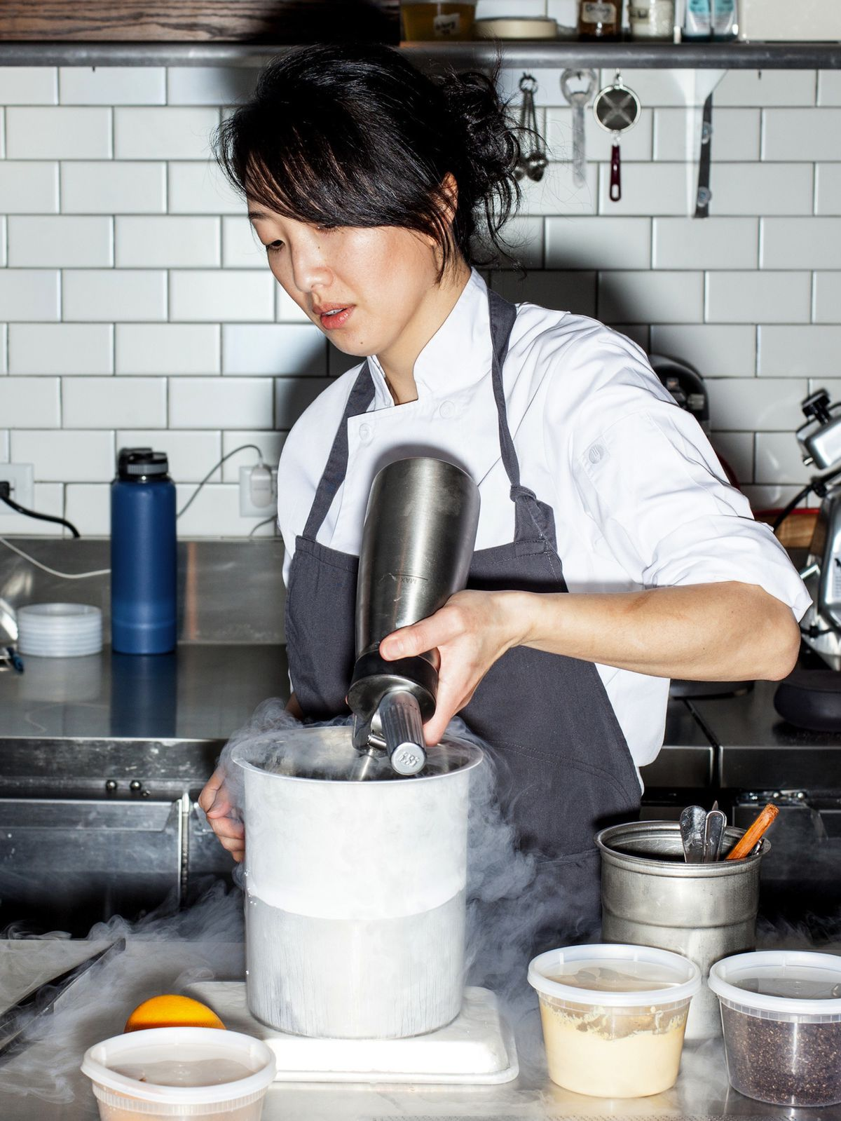 An Asian woman chef in a kitchen.