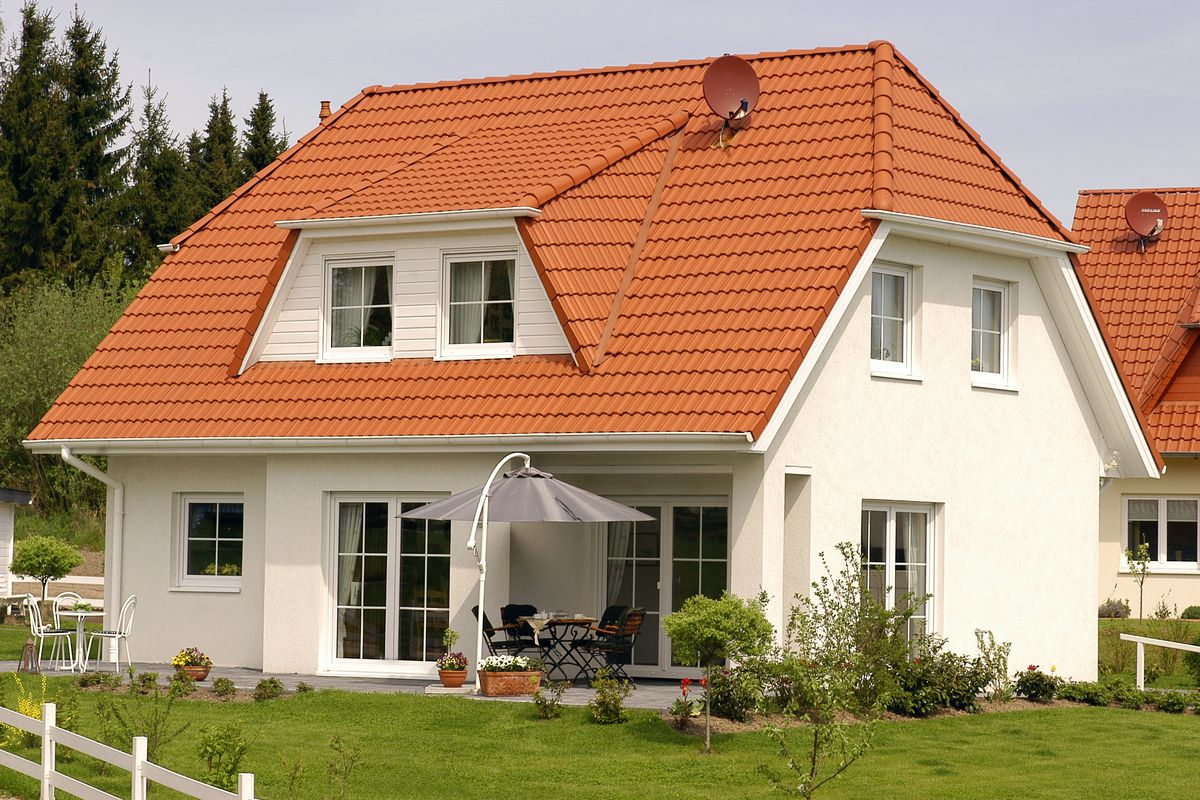 A white single-family house with an orange roof.