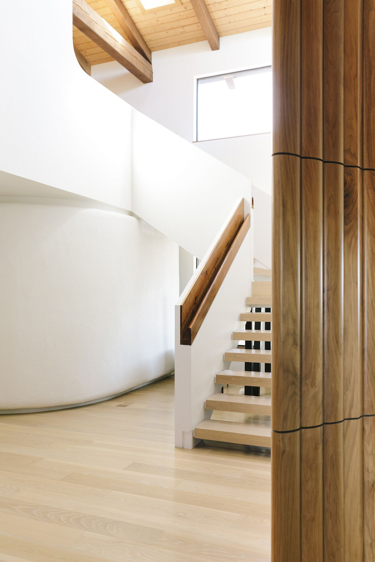 A staircase. The stairs are wooden. The walls and sides of the staircase are painted white.
