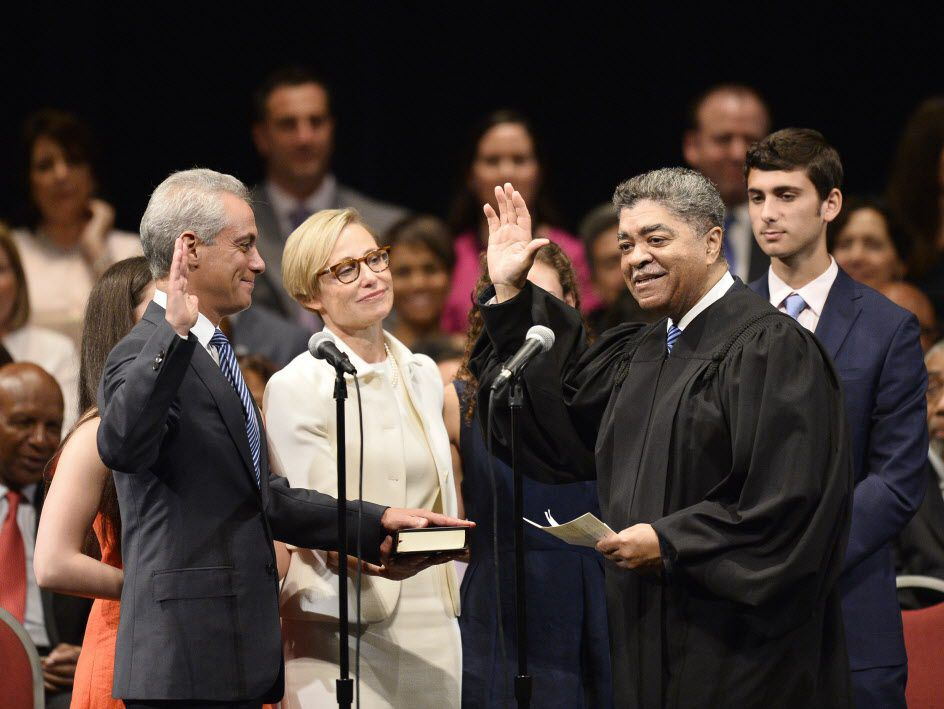 Mayor Rahm Emanuel, left, stands with his wife Amy Rule as he takes the oath of office for his second term mayor from Cook County Circuit Court Chief Judge Timothy C. Evans at the Chicago Theatre on May 18, 2015 in Chicago. (File Photo by Brian Kersey/Get