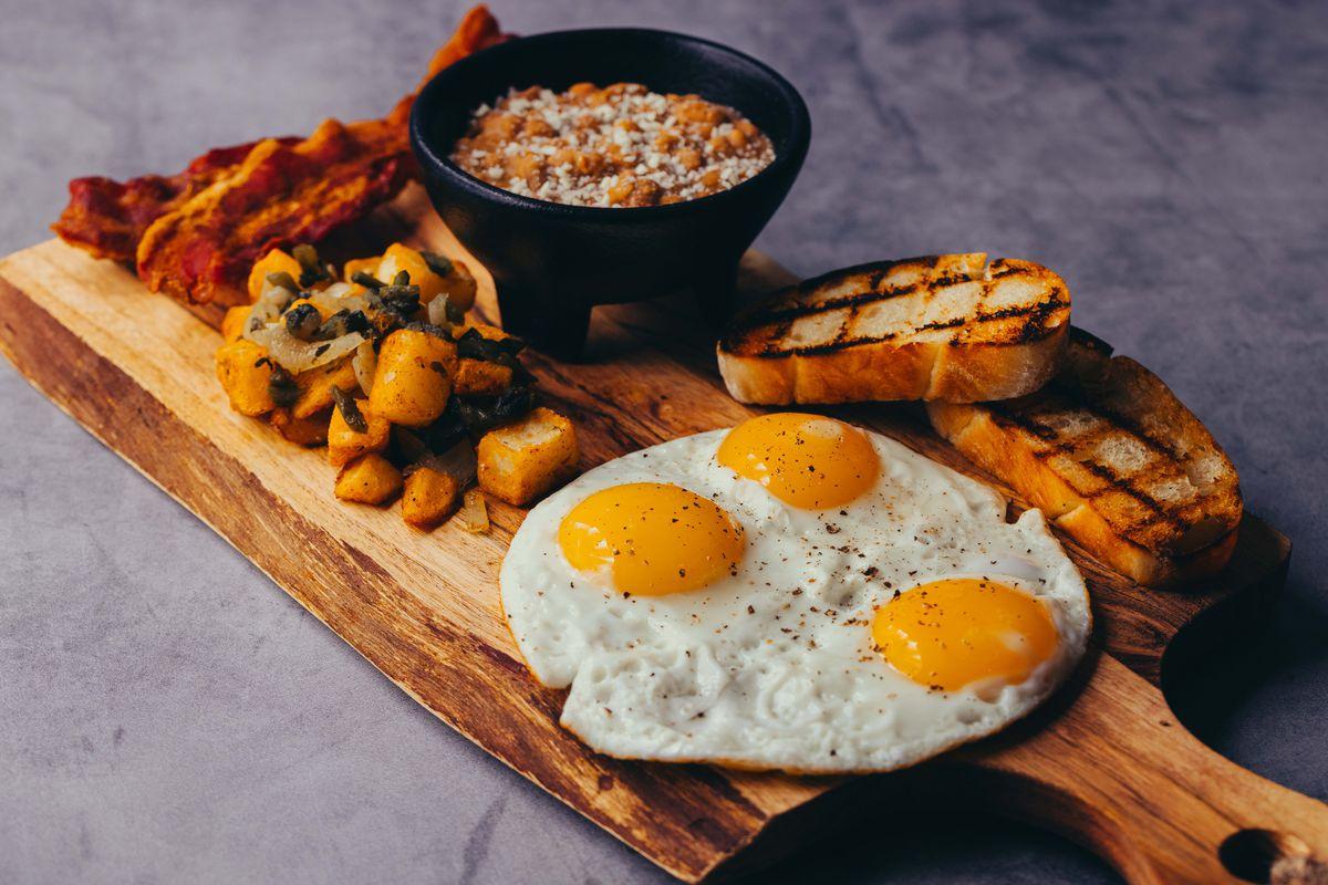 Calavera breakfast plato including three farm eggs, applewood smoked bacon, poblano-onion breakfast potato, beans, and grilled telera bread.