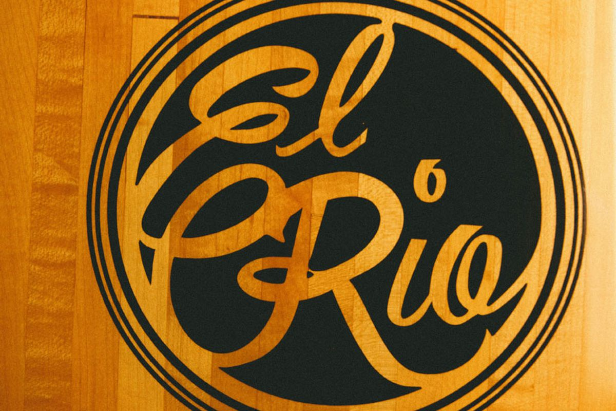 """A close up of a black logo reading """"El Rio"""" and a polished piece of wood."""