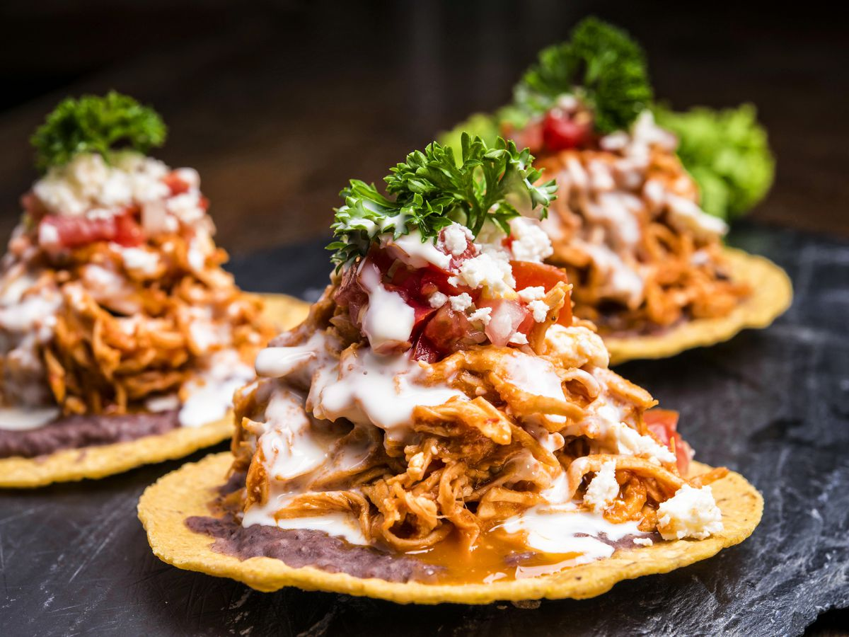Three tostadas are topped with a heaping pile of refried beans, pulled chicken tings, salsa, and sour cream