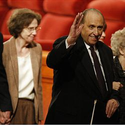 President Thomas S. Monson, with wife Frances at his side, waves to the LDS members present at general conference on Saturday.
