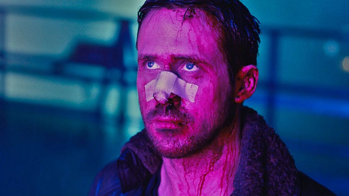 Ryan Gosling standing in purple light in the rain with a bandage on his nose
