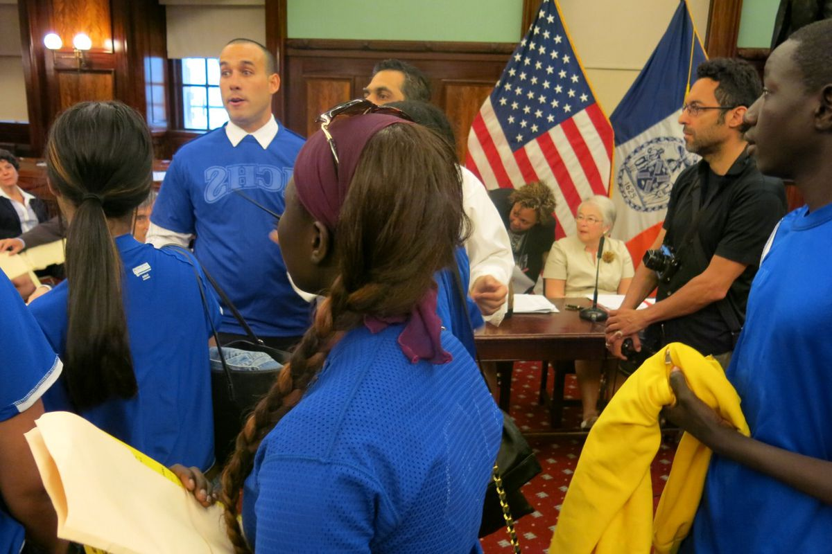 David Garcia-Rosen (left, wearing a white shirt collar and blue jersey), founder of the Small Schools Athletic League, marched into a City Council hearing with student athletes to demand funding for the league.