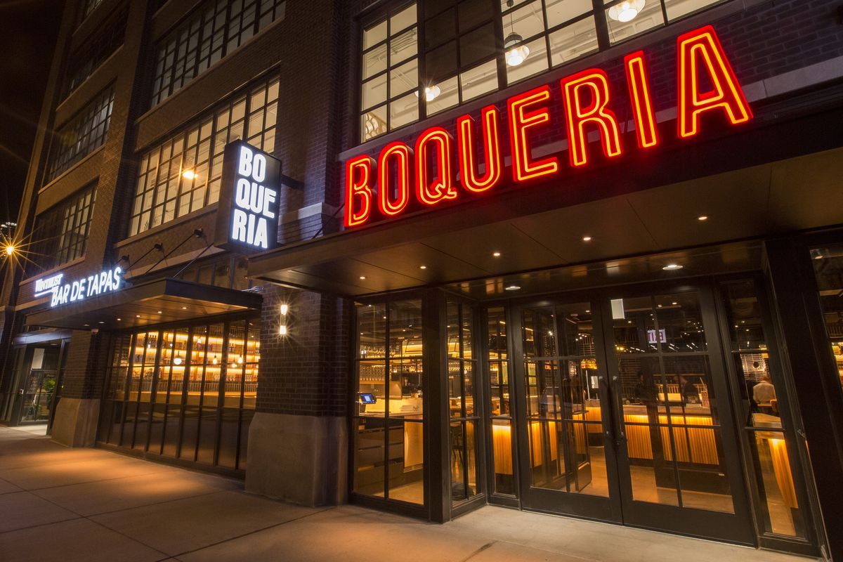 A red lit sign and the outside of a modern looking restaurant.