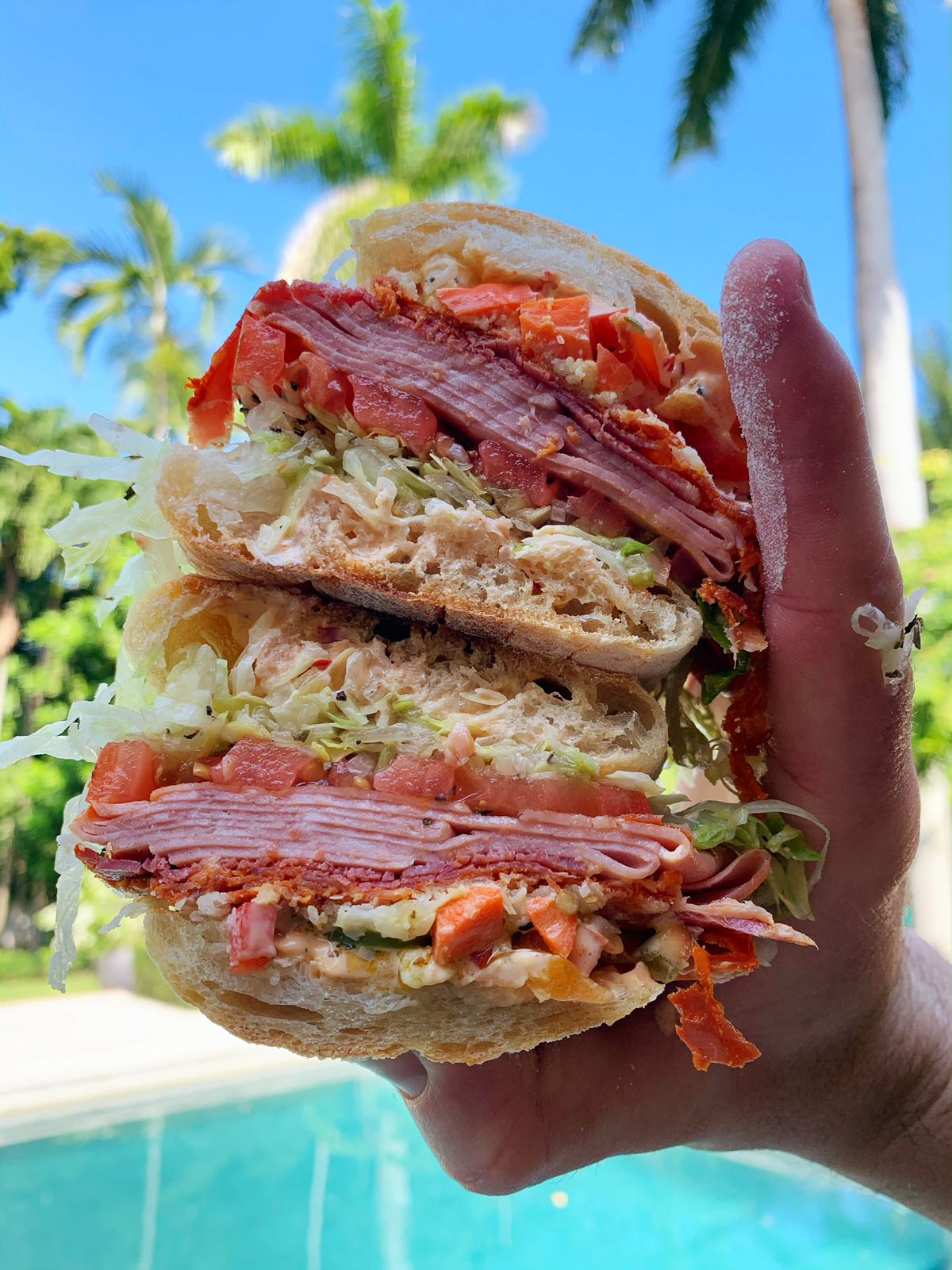 A hand is holding a sandwich with multiple layers of meat, tomatoes, and greens. A pool can be seen in the background