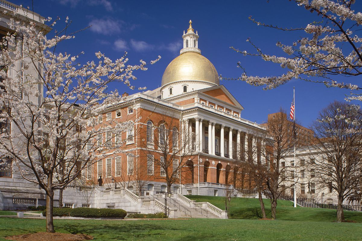 The exterior of the Massachusetts State House. The building is red brick and there is a gold dome. There are white columns on the facade.