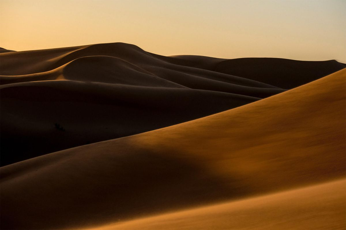 Dunes of sand. The sky matches the sand itself, blurring the horizon in the distance. It is dusk.
