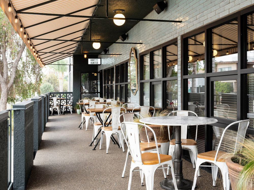 An awning over a tiled patio with white wooden tables.