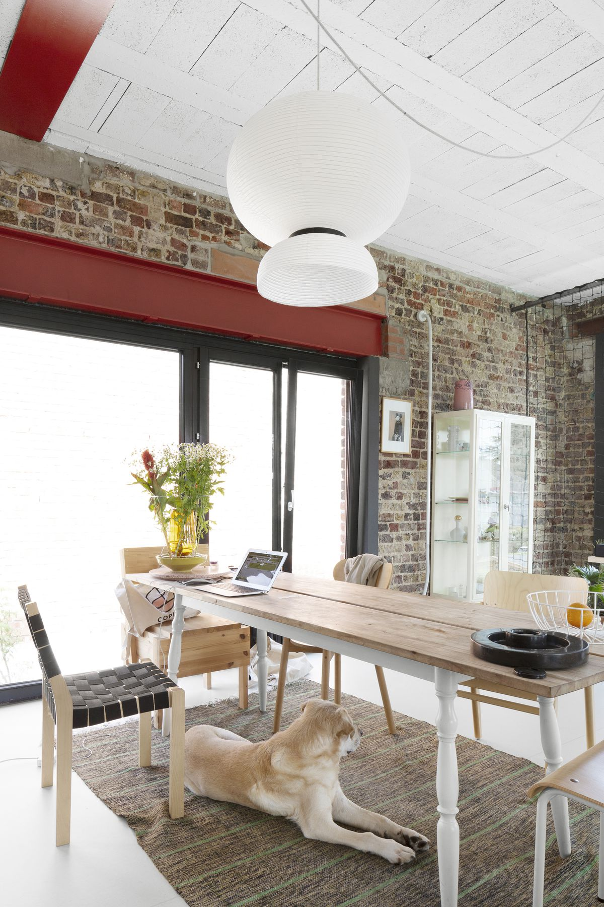 A dining area. There is a wooden table with assorted chairs. A patterned area rug is under the table. The wall is exposed brick and there is a large window. A white light fixture hangs above the table. There is a tan and white dog sitting under the table.