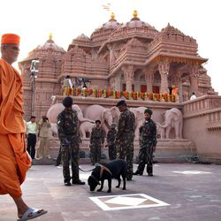 A priest walks past as security personnel stand guard during the inauguration of the Swaminarayan Akshardham Temple in New Delhi, India, Sunday, Nov. 6, 2005. India\'s Muslim president A.P.J Abdul Kalam, its Sikh prime minister Manmohan Singh and Hindu nationalist opposition leader L.K. Advani, Sunday opened one of the biggest Hindu temples of modern times, a splendid pink sandstone shrine dedicated to religious tolerance.