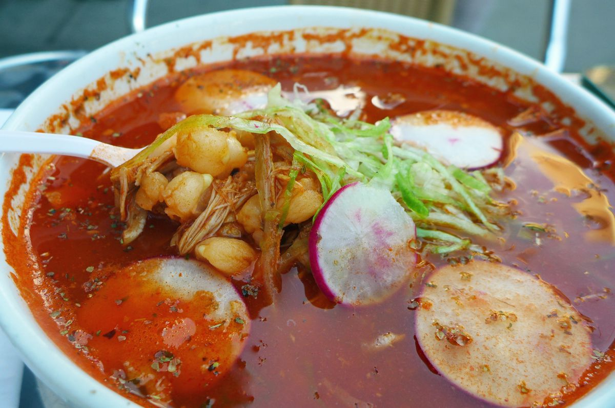 An angry red bowl of soup with radish slices, chickpeas, and shreds of chicken.
