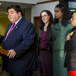 (From left) State Rep. Kelly Cassidy, Cook County State's Attorney Kim Foxx and State Sen. Toi Hutchinson hug while Gov. J.B. Pritzker speaks during a press conference at the Leighton Criminal Courthouse after Foxx filed motions to vacate more than 1,000 low-level cannabis convictions, Wednesday afternoon, Dec. 11, 2019.