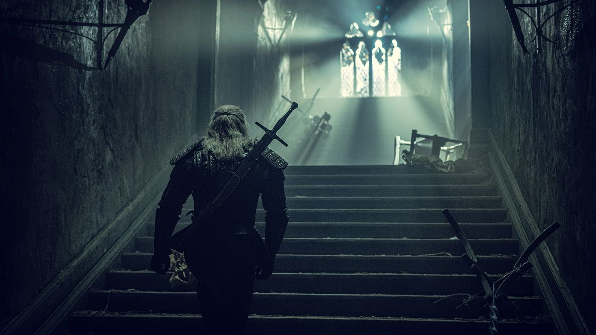 geralt walks up the stairs in a castle with light beaming out the windows