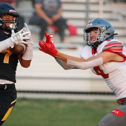 Wasatch's La'a Kalama, left, and Mountain Ridge's Jordan Day compete for a pass in a high school football game on Friday, Aug. 27, 2021, at Wasatch High School in Heber City. Mountain Ridge won 40-30.