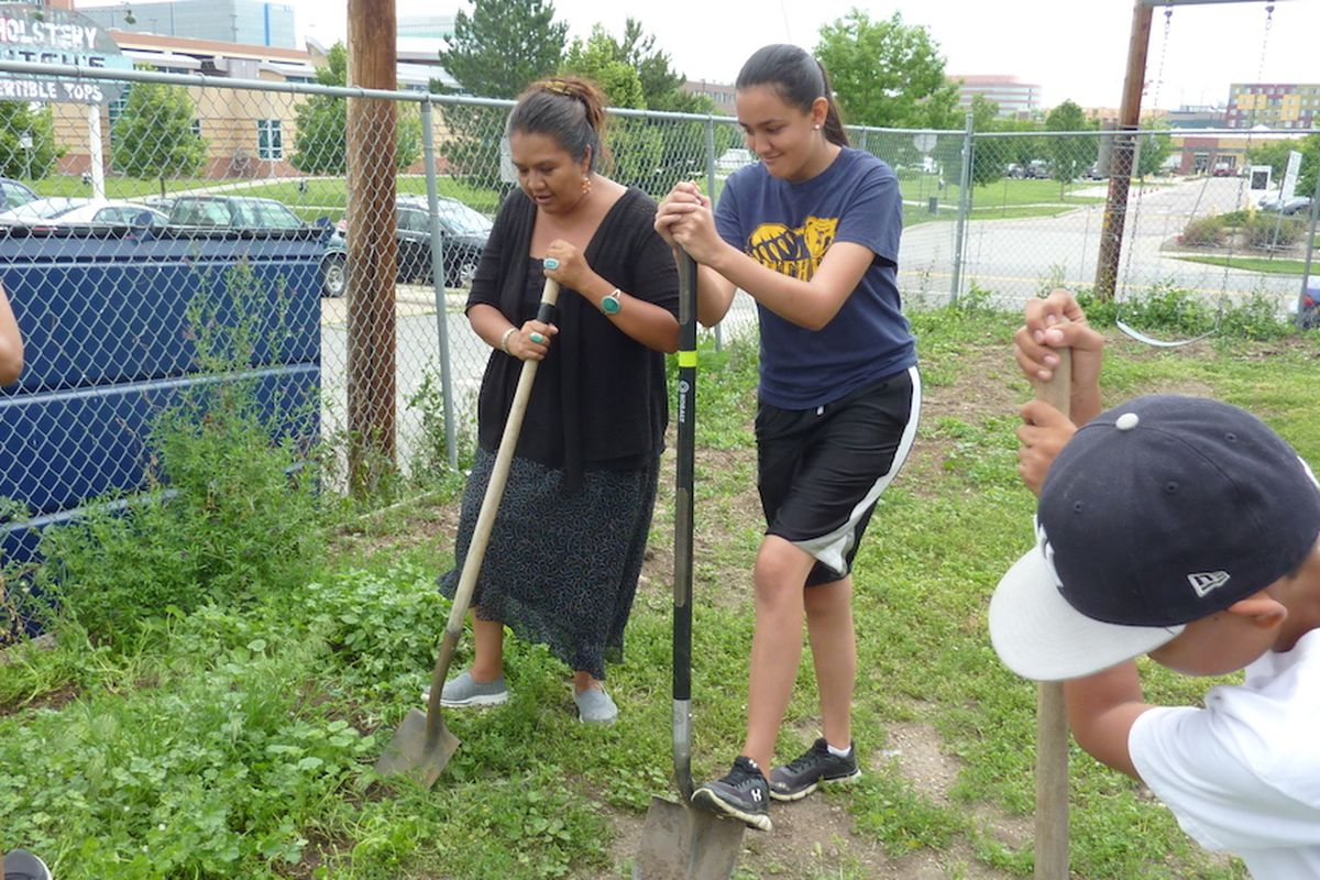 Shannon Francis and Taloa Cardinal, 15, turn soil in preparation for a garden expansion.