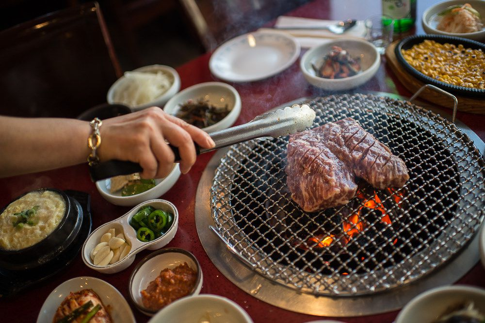 A hand grills meats on a tabletop grill, with plates of banchan on the side at Mapo Korean B.B.Q.