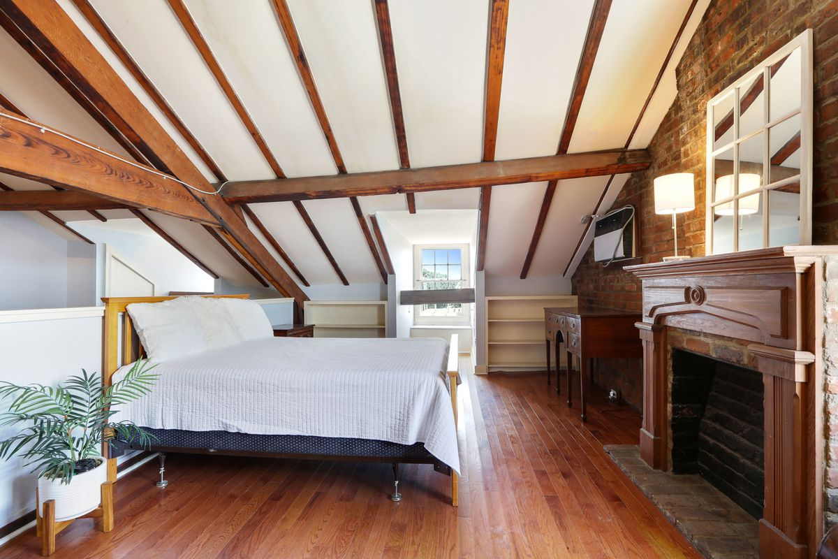 A dormer window and exposed beams frame an attic bedroom with a brick wall and fireplace.